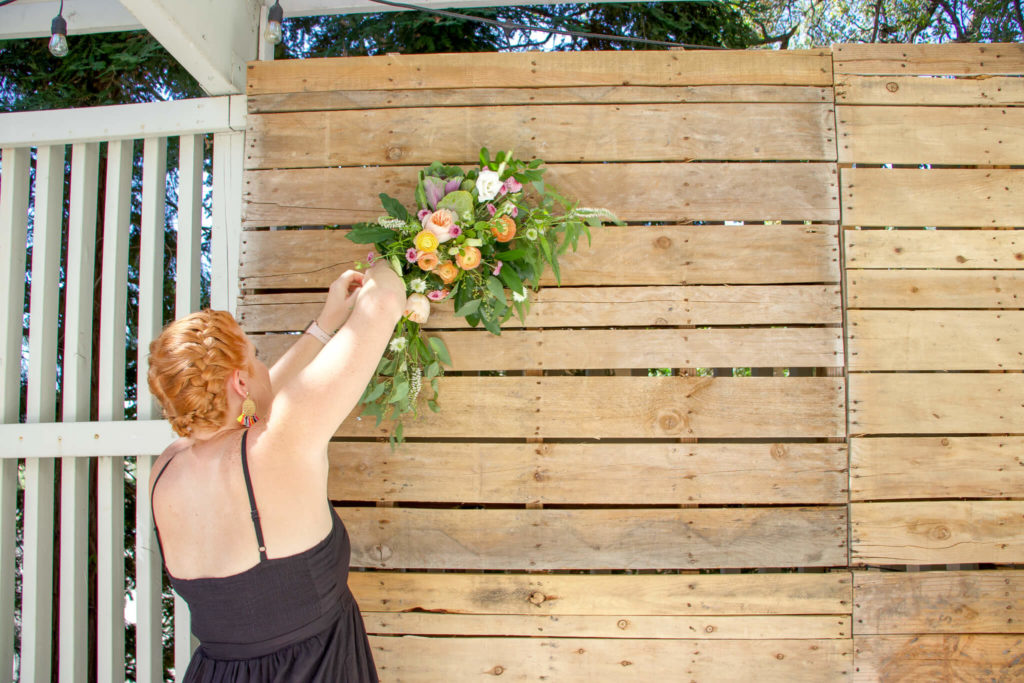 Heather placing florals on pallet wall
