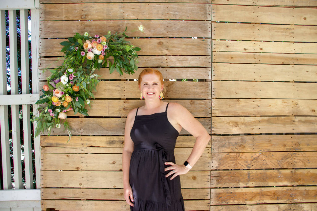Heather in front of pallet wall photo backdrop