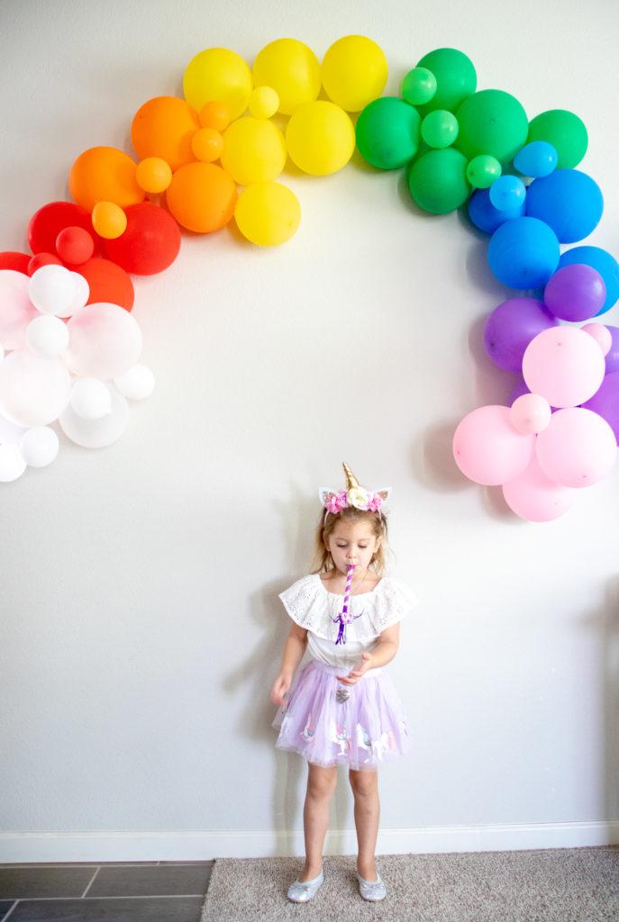 birthday girl under balloon rainbow