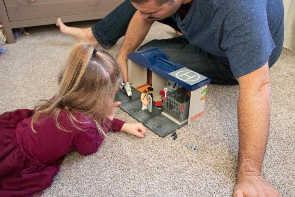 Father and daughter playing with Playmobil Take Along Police Station