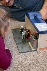 Girl looking at Playmobil Take Along Police Station