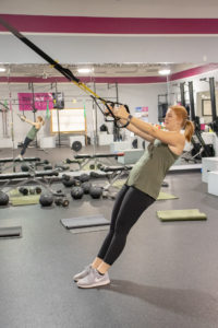 Heather using the TRX straps at Kaia Fit