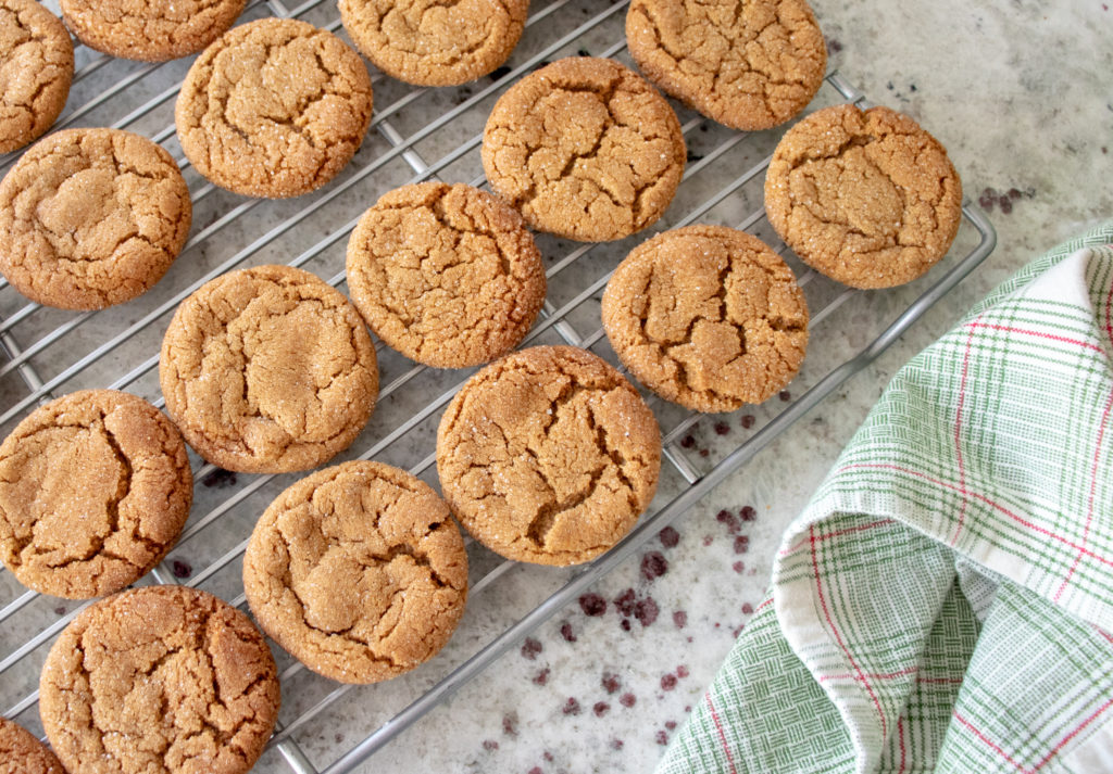freshly baked molasses cookies cooling on a baking rack on the counter
