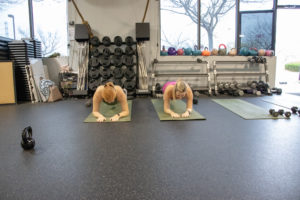 Heather and Brittany doing planks at Kaia Fit