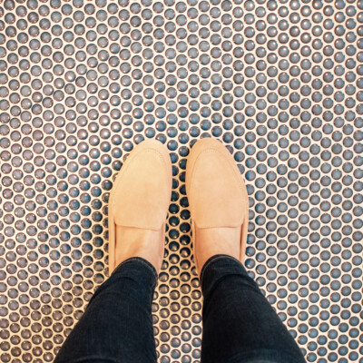 pink loafers on penny tile floor