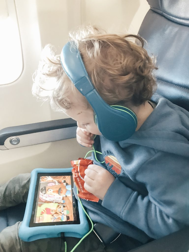 child on airplane watching a movie on his tablet