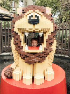 children posing in a lion made of LEGOs at Legoland California