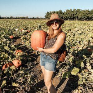 Heather posing with a pumpkin in pumpkin patch