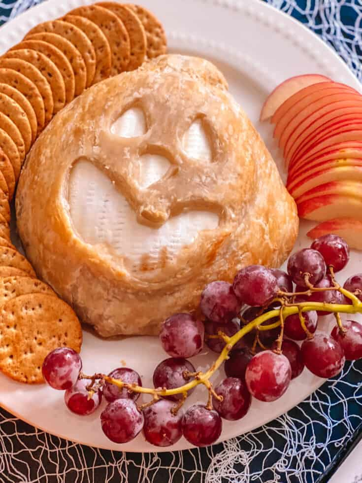 A baked brie jack-o-lantern is the perfect festive appetizer to elevate your Halloween celebration