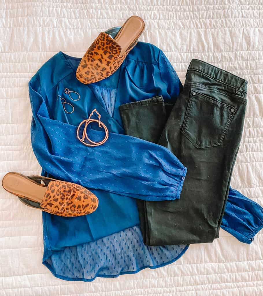 Flat lay of blue top, black jeans, leopard shoes