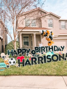 kid with balloon garland and birthday yard sign