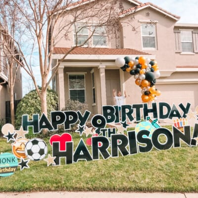 kid with balloon garland and birthday yard sign