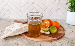Orange simple syrup on a tray with citrus fruit