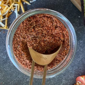 Homemade Taco Seasoning in container with measuring spoon