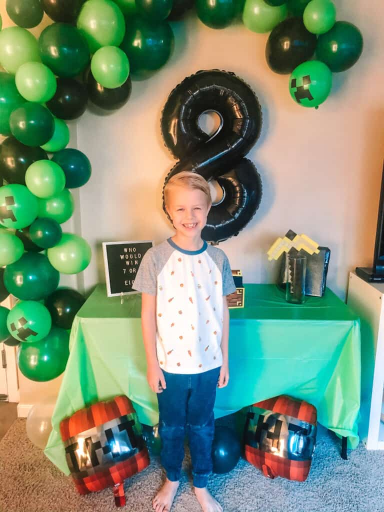 kid standing in front of balloon arch