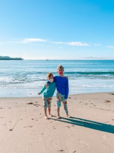 two kids on the beach wearing masks