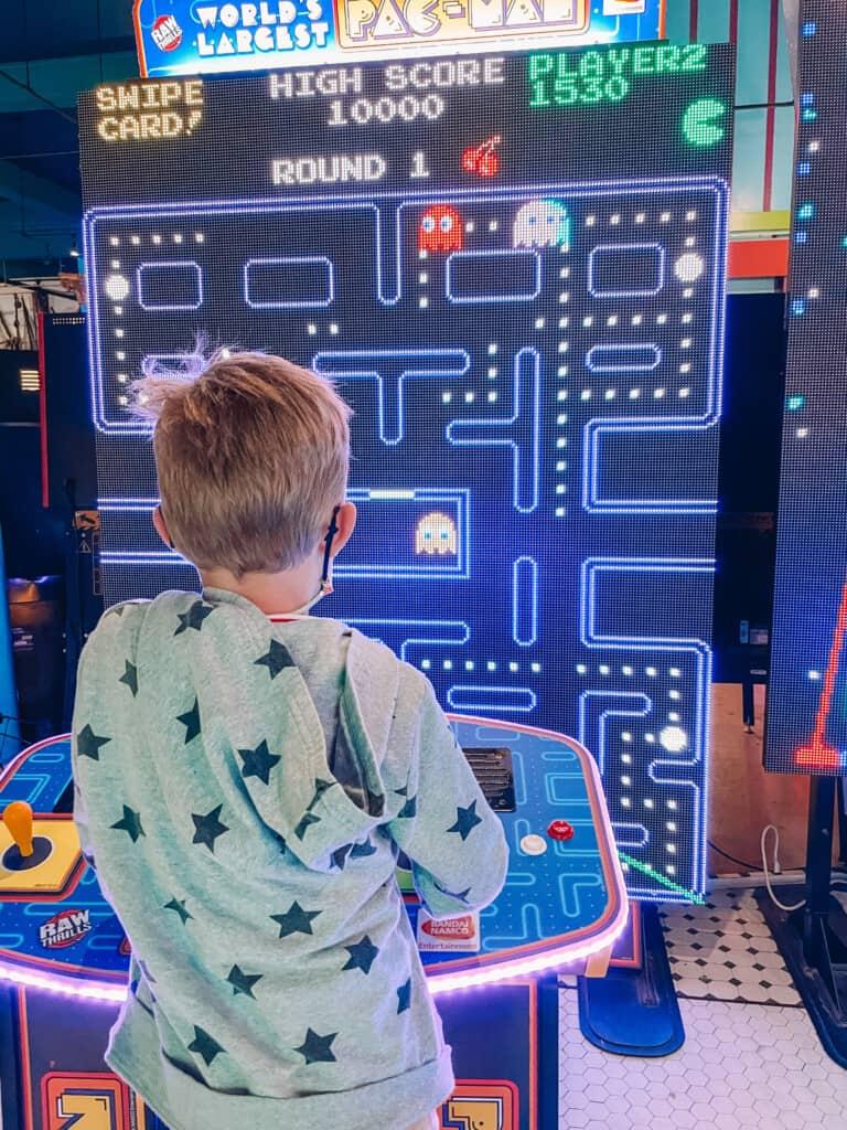 kid playing giant pac man game