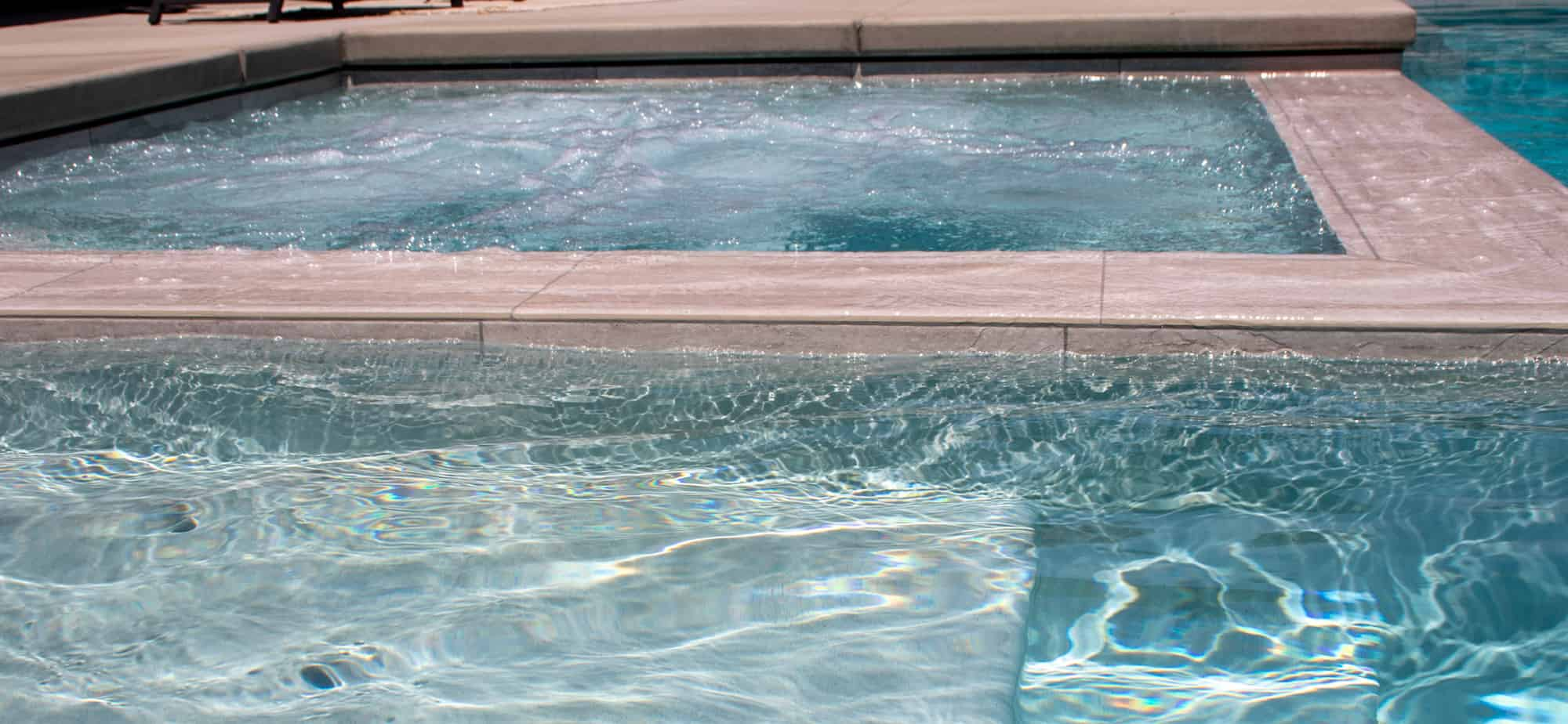 Infinity edge spa with jets on and gray waterline tile